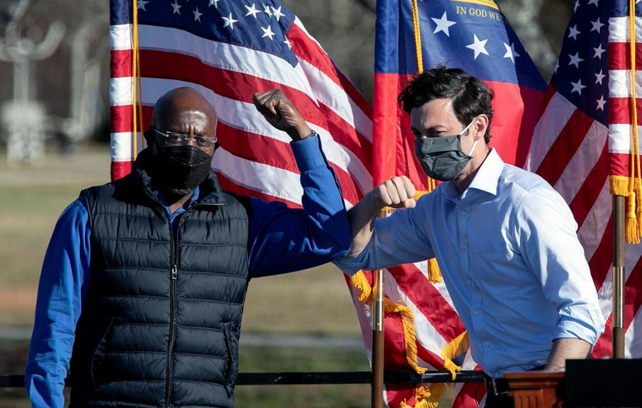 Democratic U.S. Senate candidates Raphael Warnock (L) and Jon Ossoff bump elbows during an outdoor drive-in rally in Conyers, Georgia.