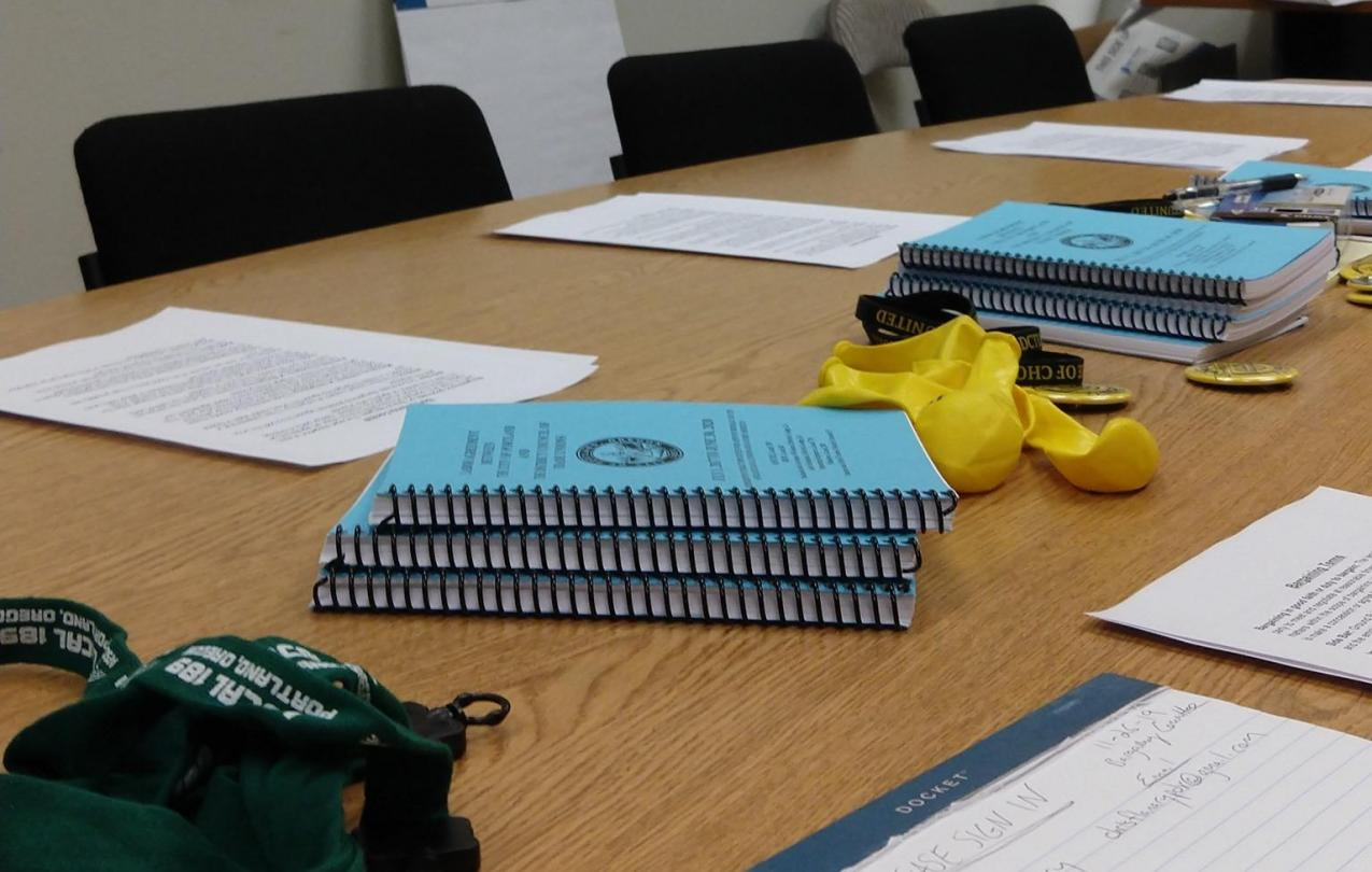 a meeting table with blue DCTU contracts, paper and pens